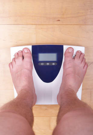 kilo: A scale with two feet of the person standing on it on a wooden floor. The scale display is empty.