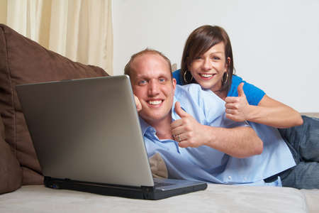 Young couple on the couch at home looking at the laptop! They both give a thumbs up sign! photo