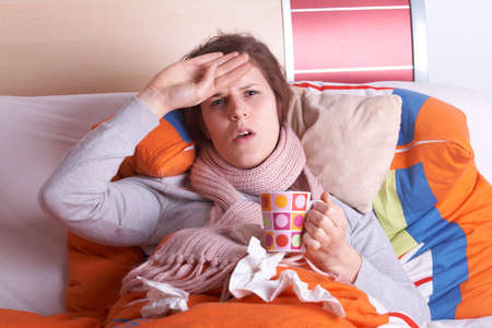 red head woman: Young woman is ill in bed. She is feeling miserable. Ideal medical shot. Stock Photo