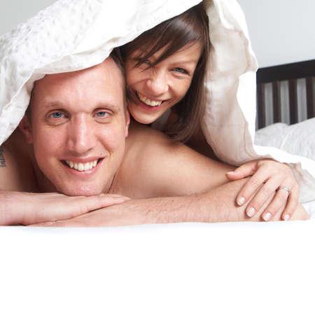 tatouage sexy: Couple de jeunes gens dans leur lit. Ils jouent dans le roman sous les draps.