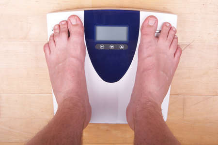 A scale with two feet of the person standing on it on a wooden floor. The scale display is empty.  photo