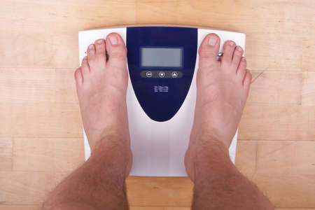 A scale with two feet of the person standing on it on a wooden floor. The scale display is empty - copyspace. photo