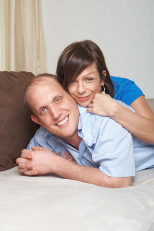 Beautiful young couple on a couch in their new appartment. photo