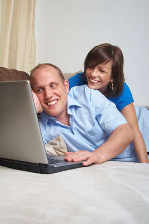 Young couple on the couch at home looking at the laptop! photo