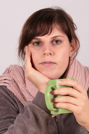 Feeling Sick - This young beautiful woman drinks a cup of tea. Her facial expression shows that she is feeling sick. photo