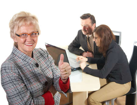 tumb: Businesswoman showing tumb up sign in office environment. Three people with focus on mature woman in front. Isolated over white.