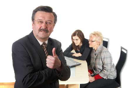 tumb: Businessman showing tumb up sign in office environment. Three people with focus on mature man in front. Isolated over white.