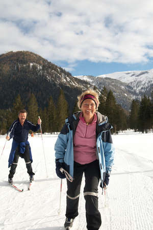 A senior couple outdoor doing cross country skiing in a winter setting. photo