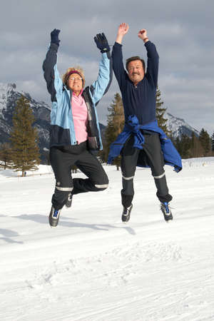 intend: A senior couple outdoor in a winter setting. The couple jumps in the air. Slight motion bluriness is intend. Stock Photo