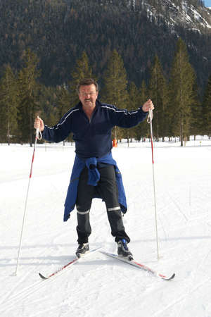 A senior man outdoor doing cross country skiing in a winter setting. photo