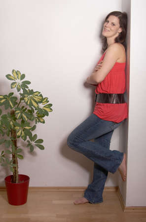 A young and sexy woman is leaning againgst a wall. She is in her new apartment with a new plant. photo