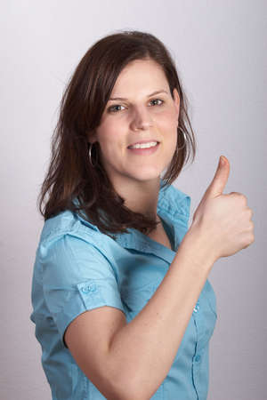 Closeup portrait of a happy young woman showing a thumps-up sign. photo