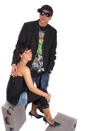 Young stylish couple isolated over white. She is sitting on dj cases. photo