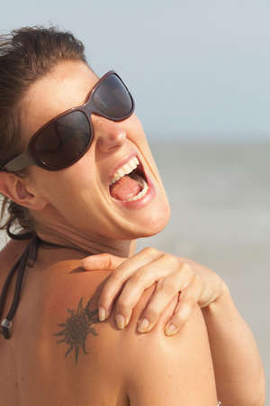 Young woman on a beach is holding her back in pain. She has a sunburn. photo