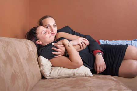 Young couple chilling on a couch at home. Both dressed up nicely. photo