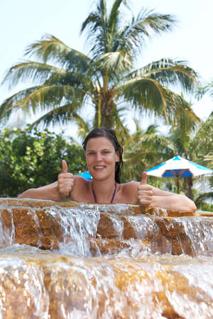 Young woman in a beautiful pool with palms in the background. She is showing a thumbs up sign. photo