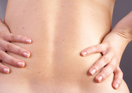 sever: Young woman with sever back pain. She is holding her schoulder. Over gray background.