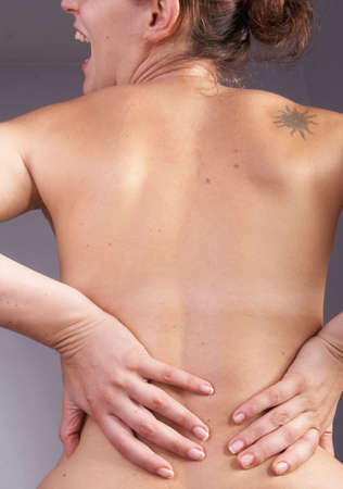 Young woman with sever back pain. She is holding her schoulder. Over gray background. photo
