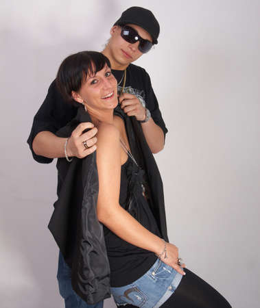 Young stylish couple is posing in style! The man helps her. photo