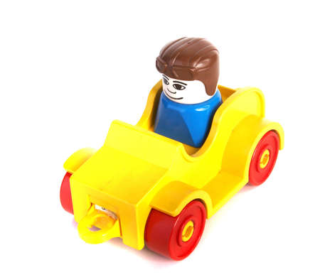 slight: Toy car with driver over white background with lots of copyspace. The car has slight shadows to show the depth.