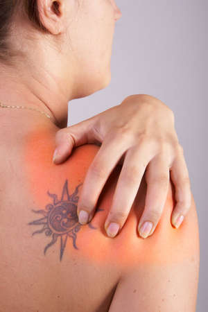 Young woman with sever back pain. She is holding her schoulder. Over grey background. She has a tattoo on her shoulder. The hurting area was saturated in red to symbolize the pain. photo