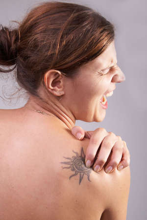 Young woman with sever back pain. She is holding her schoulder. Over grey background. She has a tattoo on her shoulder. photo