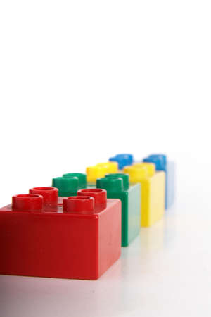 slight: Building bricks in different colors over gradient background with lots of copyspace. The bricks have slight shadows to show the depth. Stock Photo