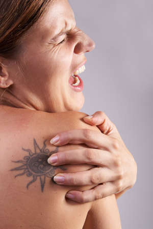 Young woman with sever back pain. She is holding her schoulder. Over grey background. photo
