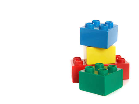 building bricks in different colors over white background with lots of copyspace. Stock Photo