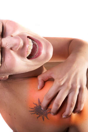 nape: Young woman with sever back pain. She is holding her schoulder. Over white background. The hurting area was saturated in red to symbolize the pain. Stock Photo