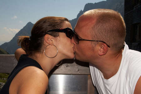 Hiking couple is relaxing and kissing in the sun on top of the mountain. Stock Photo - 5365234