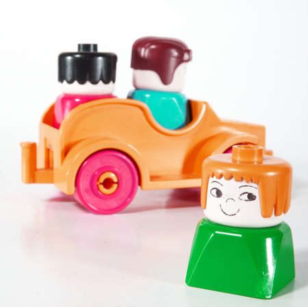 oppress: Toy car with two people driving away - leaving one alone. Shot over white background with lots of copyspace. The car has slight shadows to show the depth. Stock Photo