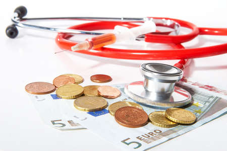 Red Stethoscope and a syringe with money - symbolizing expensive healthcare systems. photo
