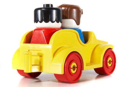 Toy car with a couple driving over white background with lots of copyspace. The car has slight shadows to show the depth. Stock Photo - 5431382