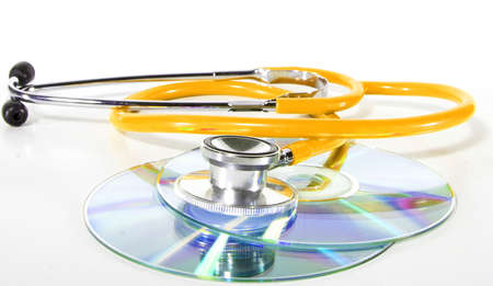 Yellow Stethoscope and a cd disk - checking the content of the disk. Could be used for medical and computer purposes! Highkey image! photo