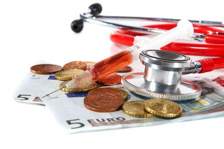 Red Stethoscope and a syringe with money - symbolizing expensive healthcare systems. Highkey image! photo