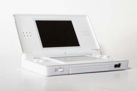 portables: A white console over a grey background. Stock Photo