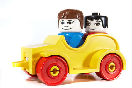 Toy car with a couple driving over white background with lots of copyspace. The car has slight shadows to show the depth.