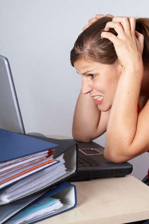 Young woman sitting at her laptop with a lot of work in front of her. She is very frustrated. photo