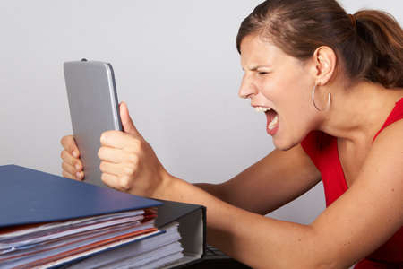 Young woman sitting at her laptop with a lot of work in front of her. She is very frustrated. Stock Photo - 5496801