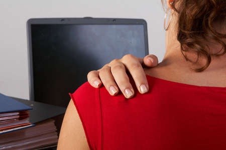 Young woman sitting at her laptop with a lot of work in front of her. She has a pain in her neck  back. photo
