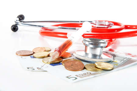 hospital expenses: Red Stethoscope and a syringe with money - symbolizing expensive healthcare systems. Highkey image!