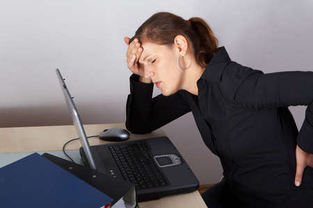 Young woman sitting at her laptop with a lot of work in front of her. She has a pain in her neck / back. Stock Photo - 5582912