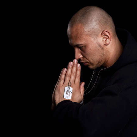 A young asian man with a hoddie is praying over black photo