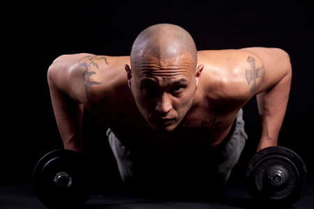 bodybuilding boy: Young bald strong man is working out over black background.