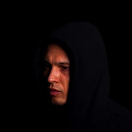 casual hooded top: Stylish young man with hoddie over a black background.