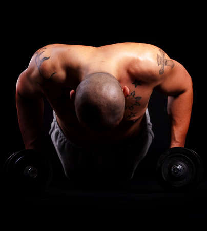 muscular build: Young bald strong man is working out over black background.
