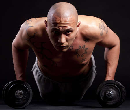 boy body: Young bald strong man is working out over black background.