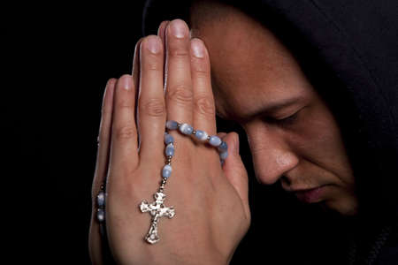 jesus adolescent: A young asian man with a hoddie is praying over black