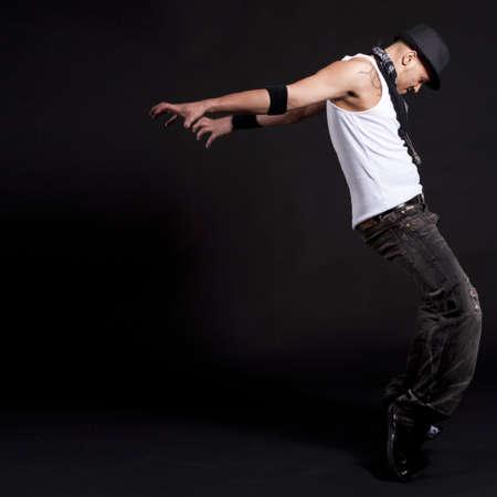 dance music: Jonge stijlvolle Aziatisch danser in de voorkant van zwarte achtergrond verplaatsen naar hip jop muziek.